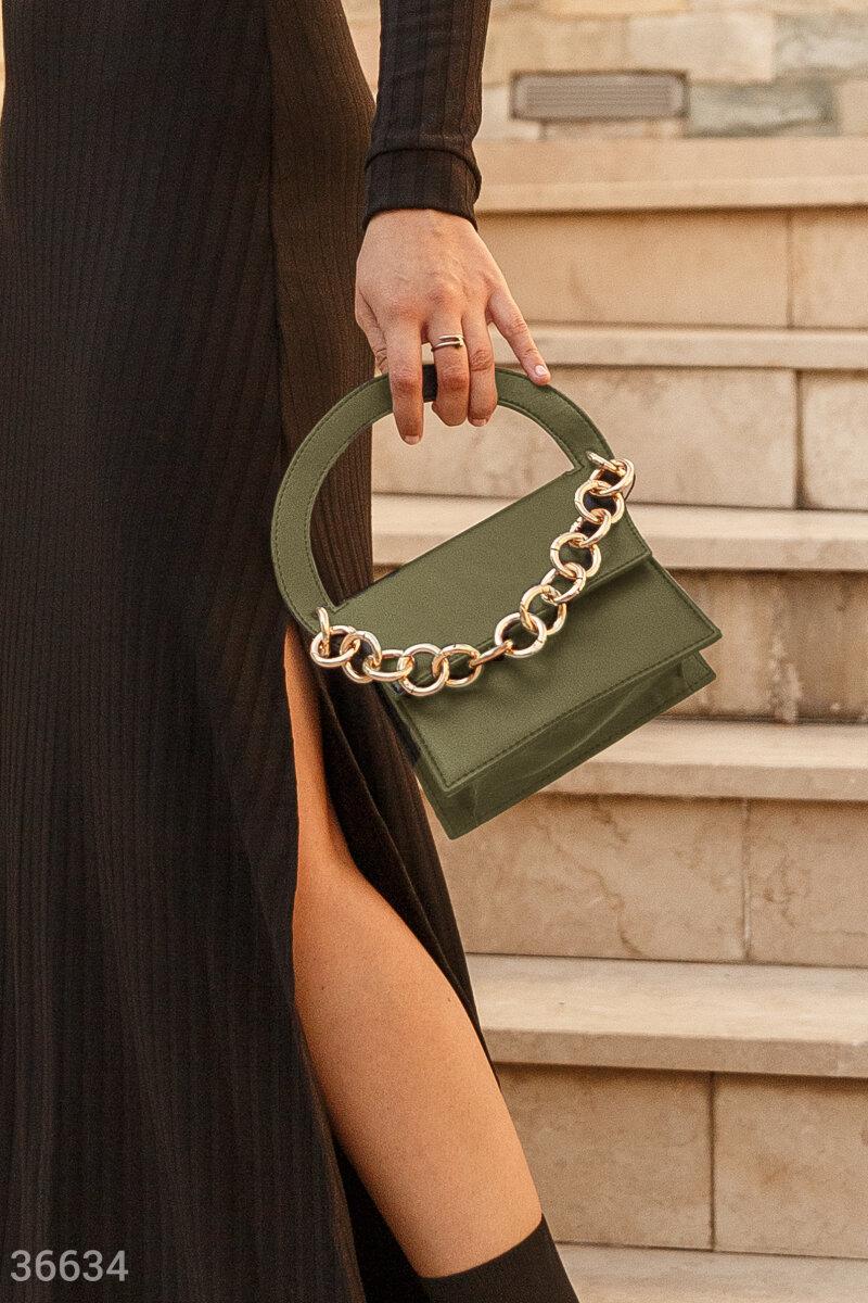 Маленькая сумка цвета хаки поможет вывести на новый уровень любой наряд. Правильное настроение задает нейтральный цвет и оригинальный дизайн с жесткой полукруглой ручкой. Крупная металлическая цепь вносит элемент дерзости. Во внутреннем отделении сделан н