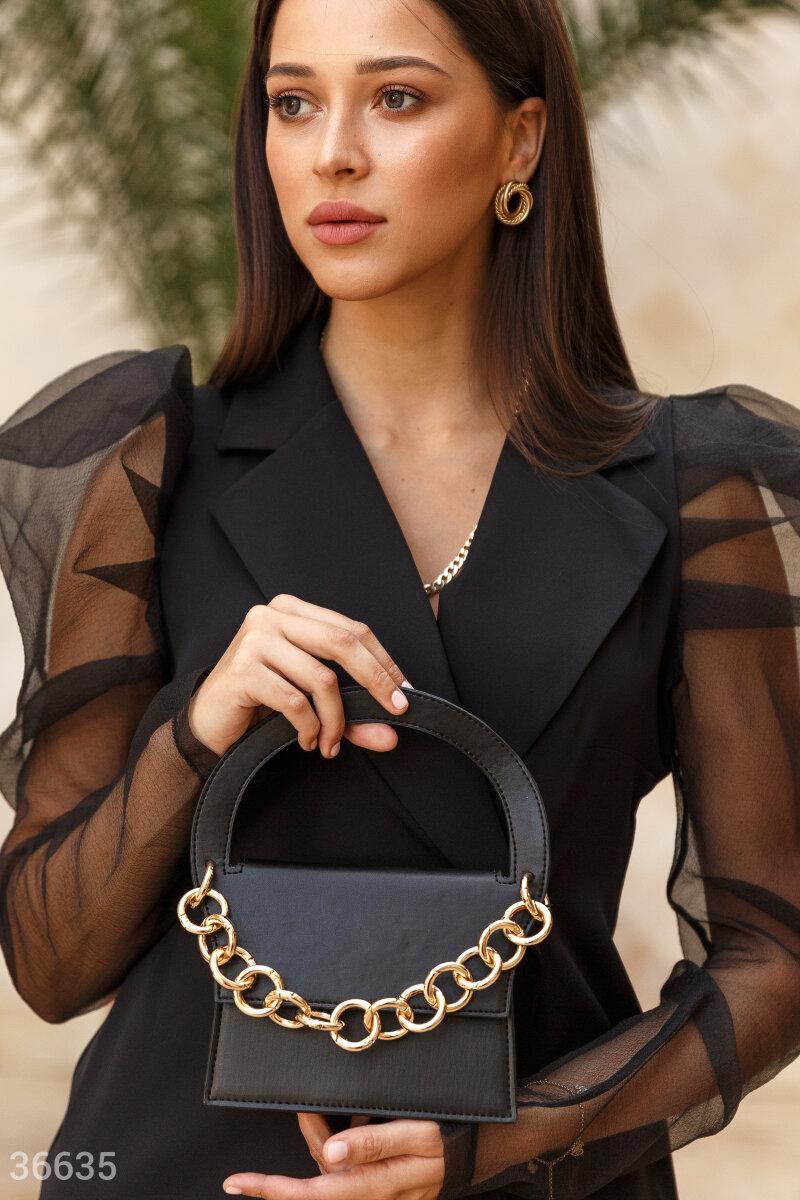 Маленькая сумка черного цвета поможет вывести на новый уровень любой наряд. Правильное настроение задает нейтральный цвет и оригинальный дизайн с жесткой полукруглой ручкой. Крупная металлическая цепь вносит элемент дерзости. Во внутреннем отделении сдела