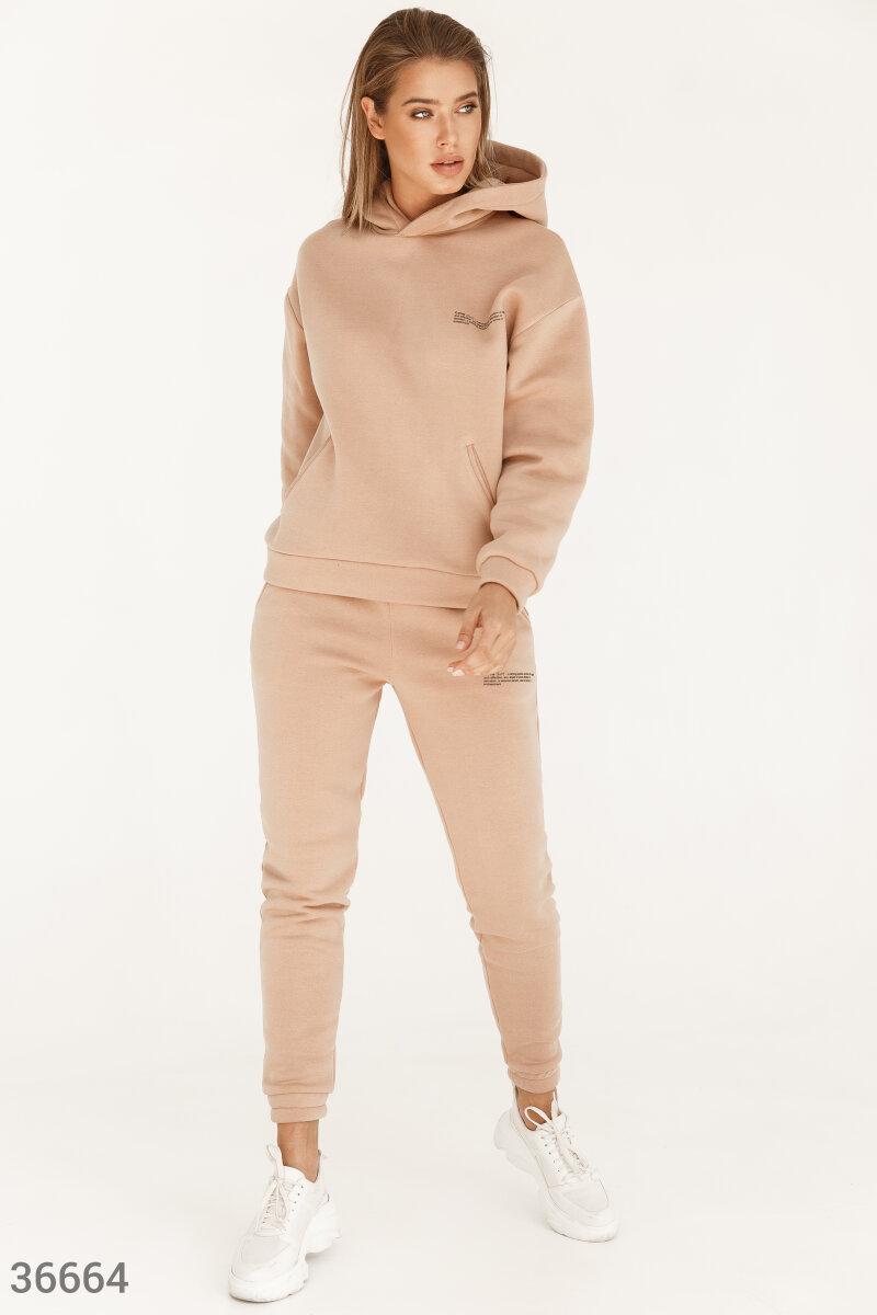 Бежевый спортивный костюм сделан из мягкого хлопкового материала с внутренним флисовым слоем. Свободная толстовка с капюшоном и брюки-джоггеры отлично смотрятся как в комплекте, так и по отдельности. На переднюю сторону модели нанесен минималистический пр