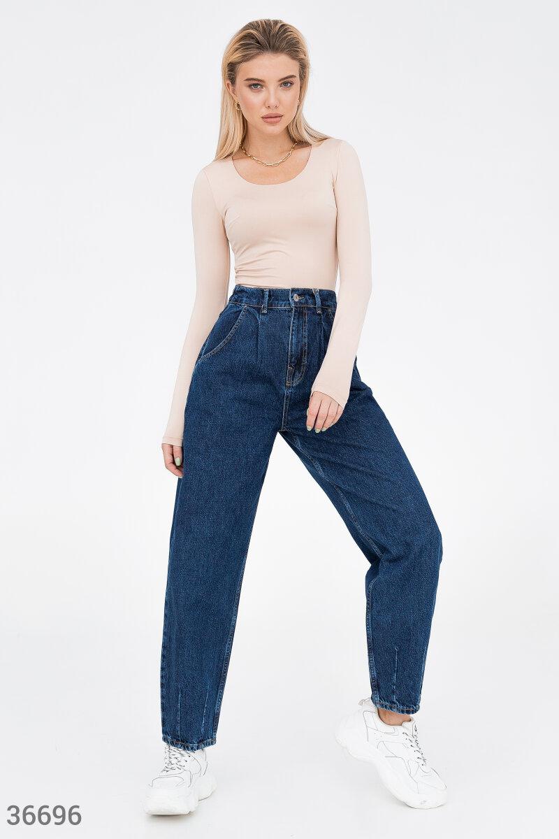 Сочетание синего оттенка и трендового фасона делает джинсы выгодным приобретением. Для производства модели использован мягкий хлопок. Свободный крой дополнен защипами на нижней кромке брючин и на поясе. Для комфорта в изделии сделаны четыре кармана.