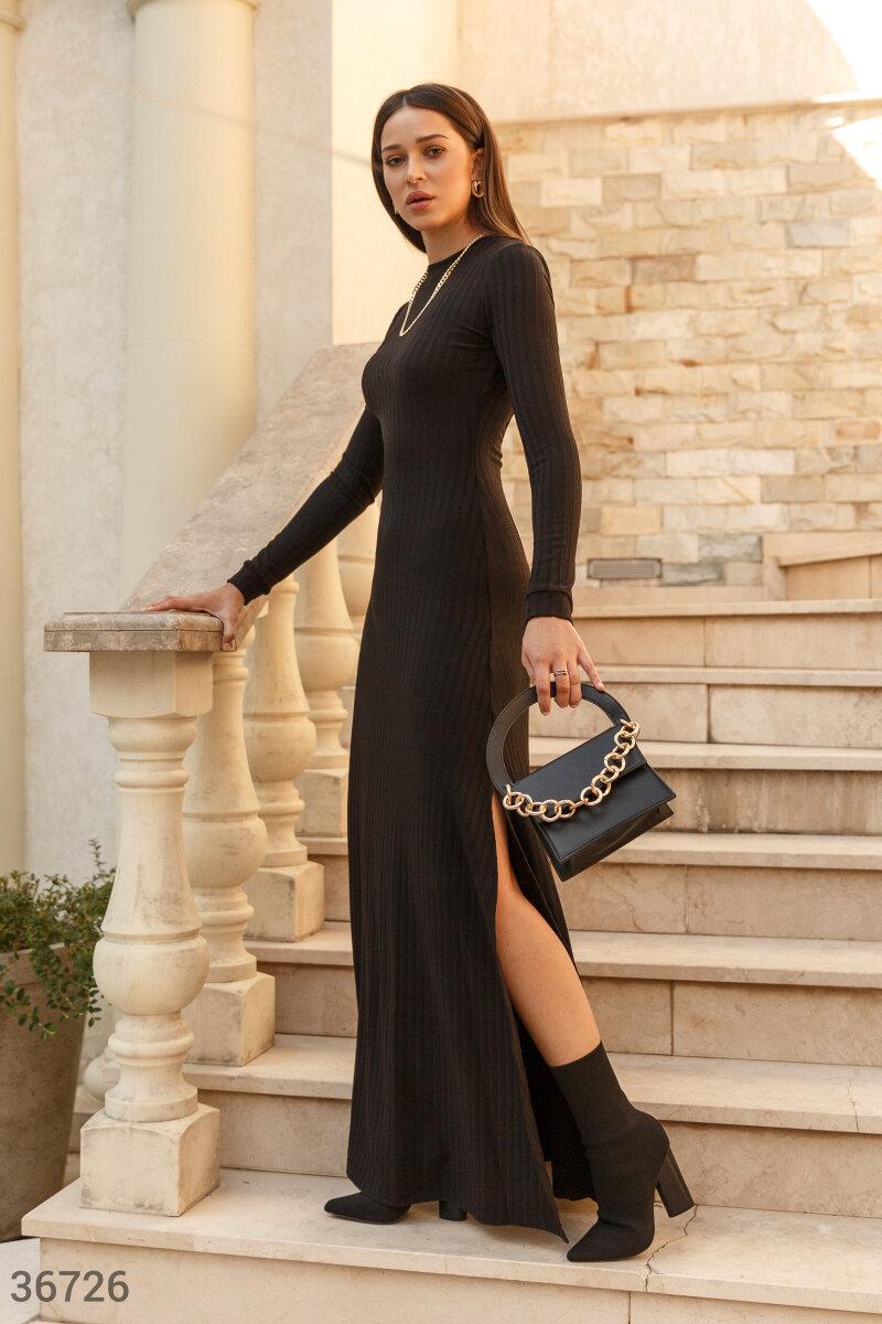 Платье-макси из фактурного мягкого трикотажа. Модель универсального черного цвета дополнит образ в любом стиле, в зависимости от подобранных аксессуаров. Пикантный акцент вносит круглый вырез на спине. Высокие боковые разрезы на юбке выгодно открывают ног