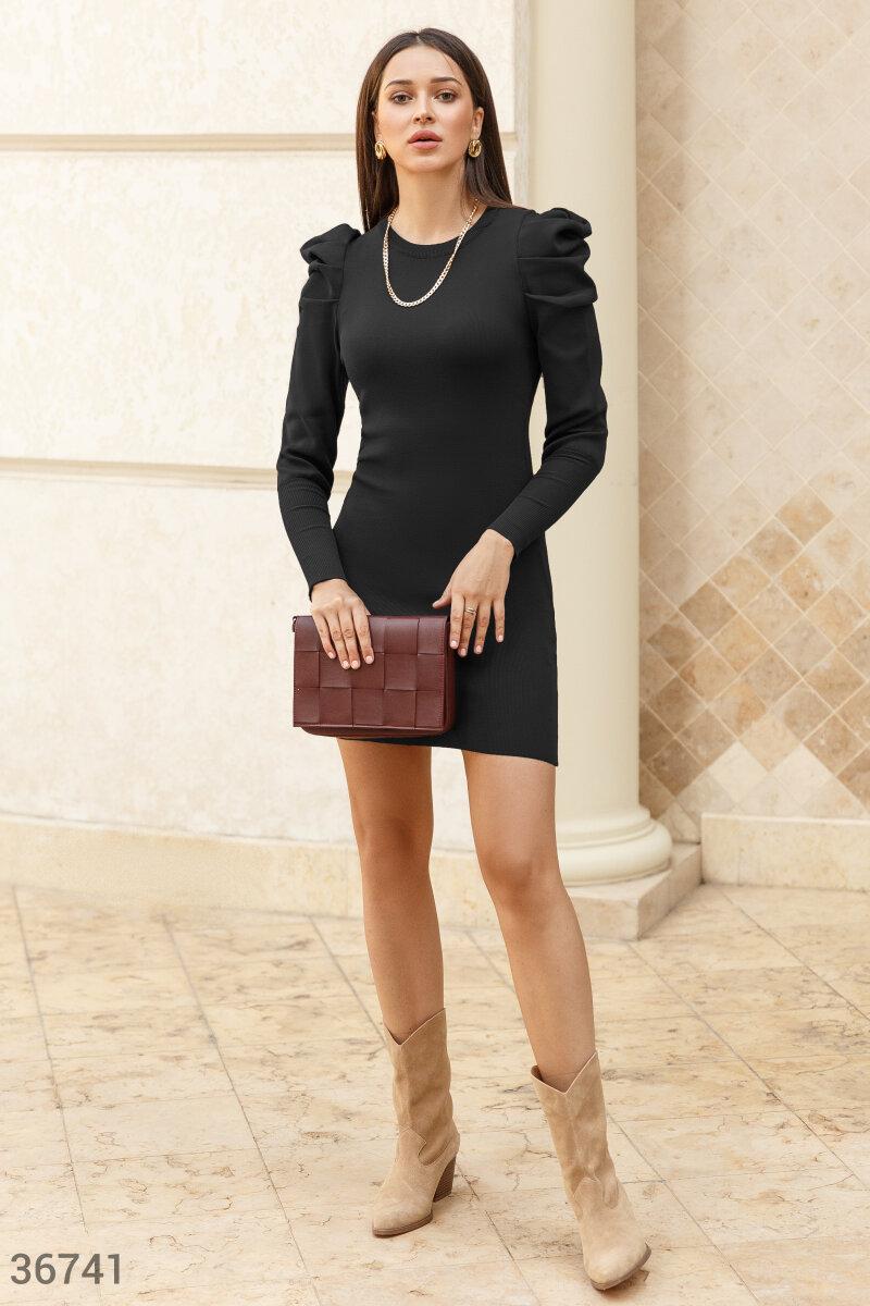 Платье-мини нейтрального черного цвета. Модель облегающего кроя дополнена акцентными защипами на плечах и длинными рукавами на широких эластичных манжетах.