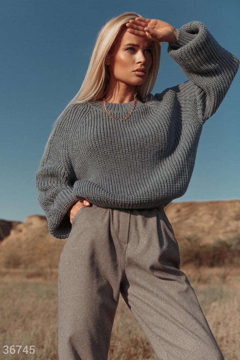 Джемпер в джинсовом оттенке сможет сделать уютным любой образ. Секрет кроется в мягкой приятной пряже на основе шерсти, которая не колется и при этом согревает. Вязаное полотно выглядит объемно и придает модели фактурности. Эластичные манжеты на рукавах и