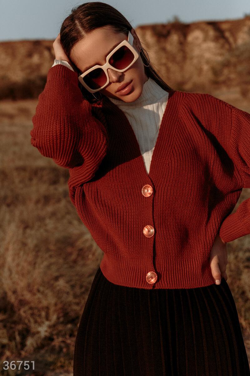 Укороченный кардиган трендового миндального оттенка гармонично дополнит повседневный образ с джинсами и майкой. Модель выполнена из фактурного вязаного трикотажа. Изделие со свободным кроем дополнено v-образным вырезом, подчеркивающим зону декольте. Карди