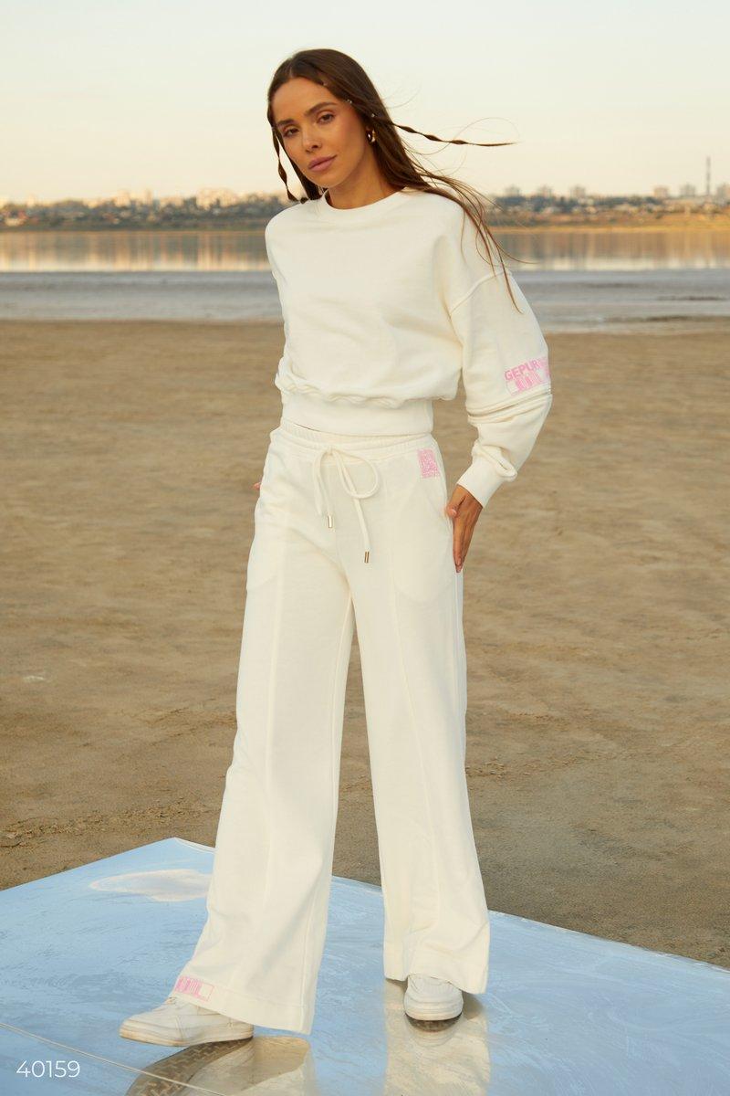 Молочные брюки палаццо, выполненные из смесового хлопка, дополнены дизайнерами Gepur эластичной вставкой и шнуровкой в поясе для вашего комфорта. Тренд на широкие брюки успешно закрепился и продолжает быть актуальным в сезоне FW 2021/22. В сочетании с ove
