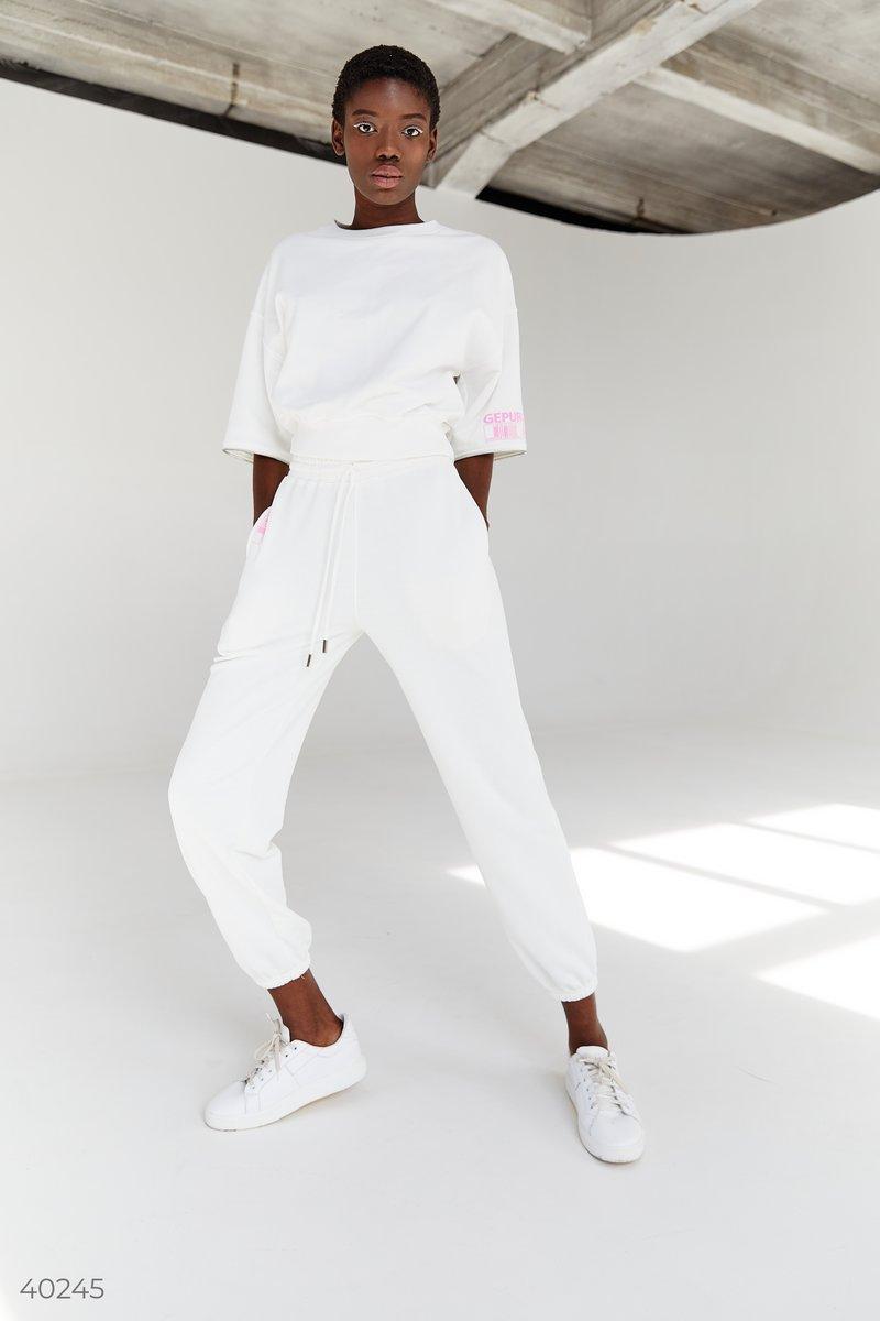 Трикотажные джоггеры молочного цвета от дизайнеров Gepur, выполнены из смесового хлопка. Модель представлена с эластичной вставкой в талии и по низу изделия, шнуровкой в поясе и карманами. Для создания спортивного образа вы можете сочетать джоггеры с толс