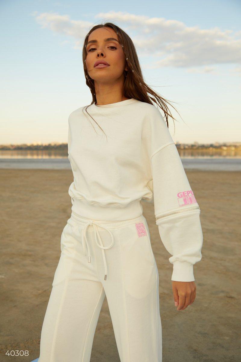 Базовый молочный свитшот, выполнен из смесового хлопка. Модель стилизована дизайнерами Gepur молниями на рукавах, которые позволяют добавить модели изюминку, расстегнув их частично, или же полностью. Такой свитшот отлично будет смотреться с джинсами, или