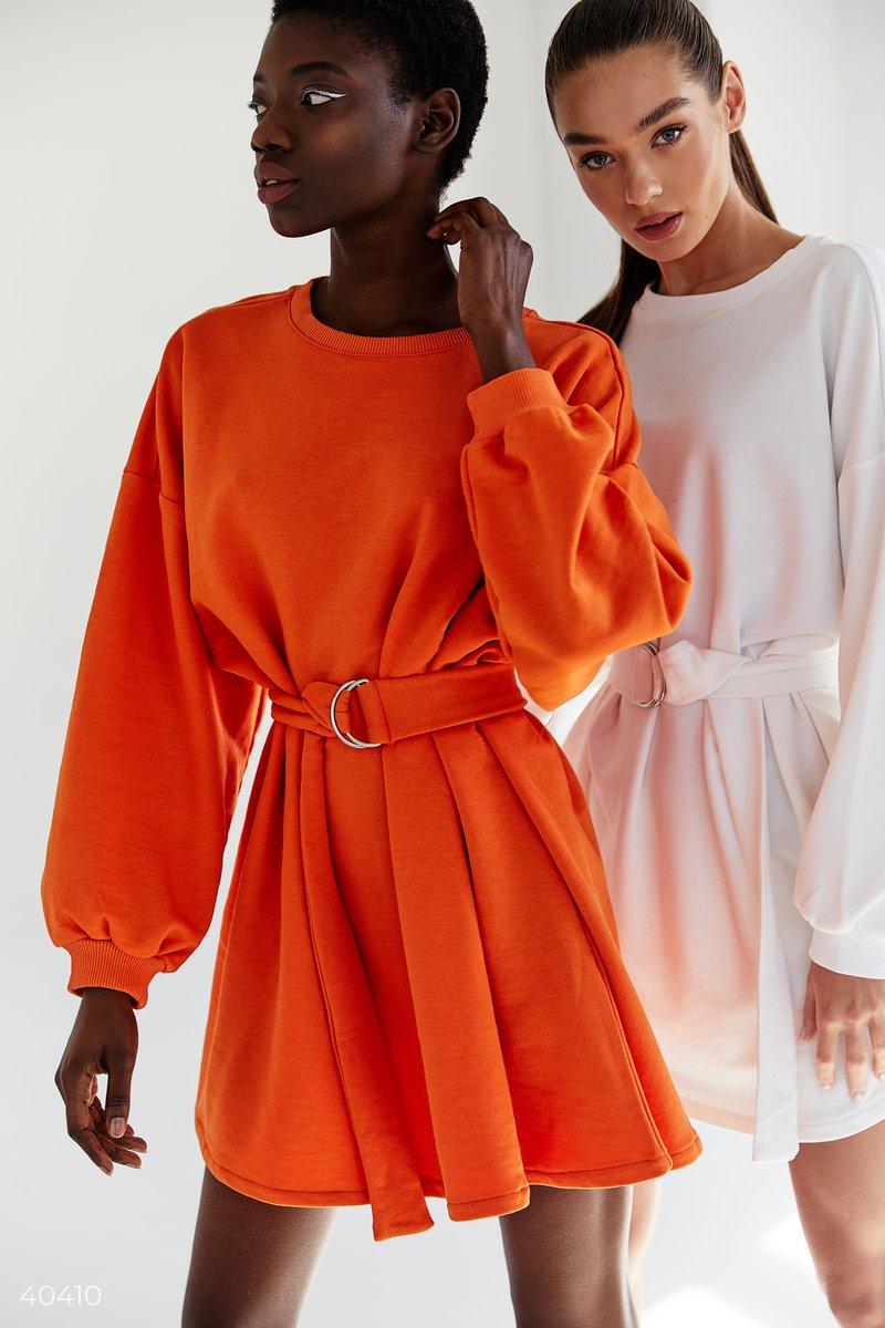 Оранжевое трикотажное платье, выполненное из смесового хлопка. Модель свободного кроя с широкими рукавами, в комплекте пояс с пряжкой. За счет универсальности модели вы сможете носить его самостоятельно, или же поверх джинсов в качестве верха. Стилизовав