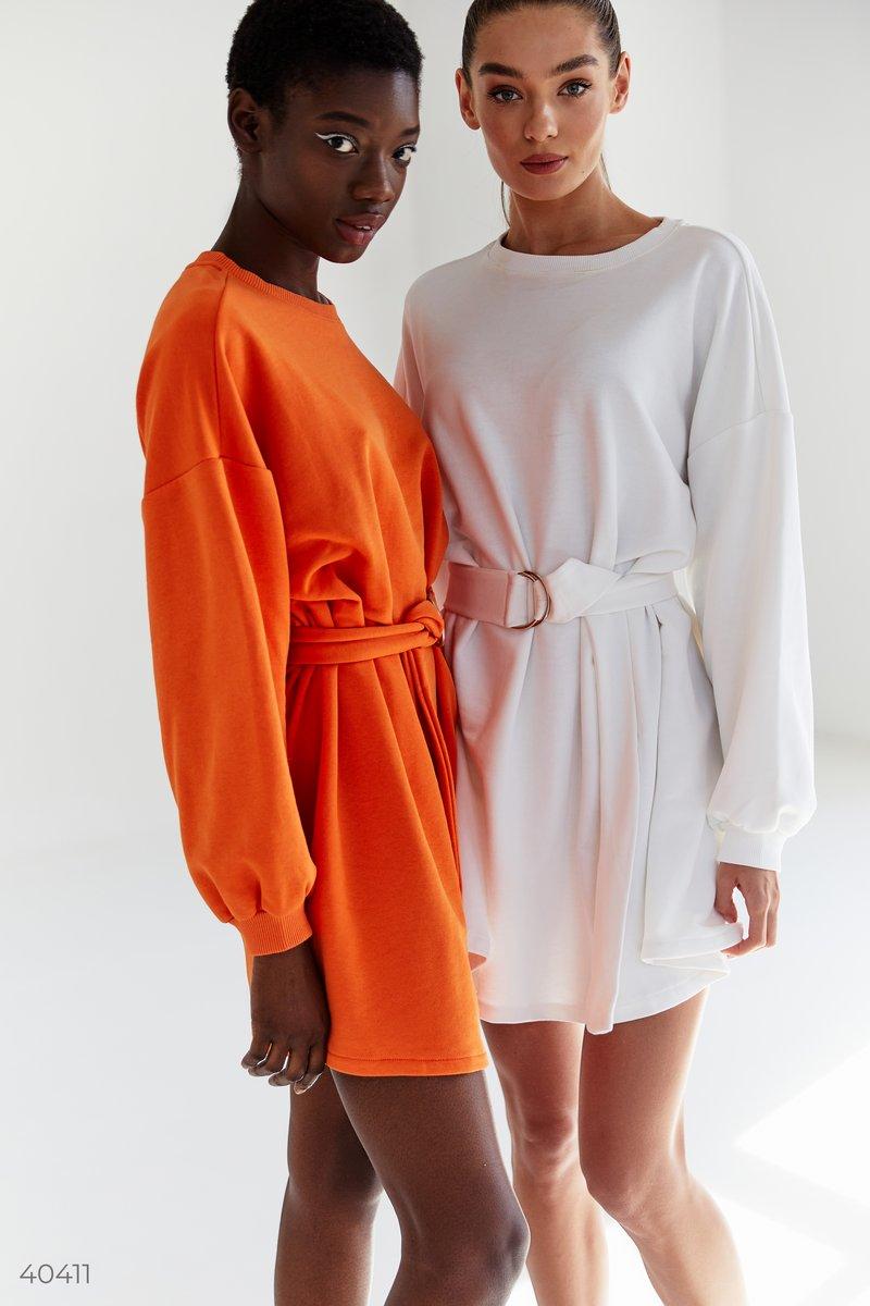 Белое трикотажное платье, выполненное из смесового хлопка. Модель свободного кроя с широкими рукавами, в комплекте пояс с пряжкой. За счет универсальности модели вы сможете носить его самостоятельно, или же поверх джинсов в качестве верха. Стилизовав наря
