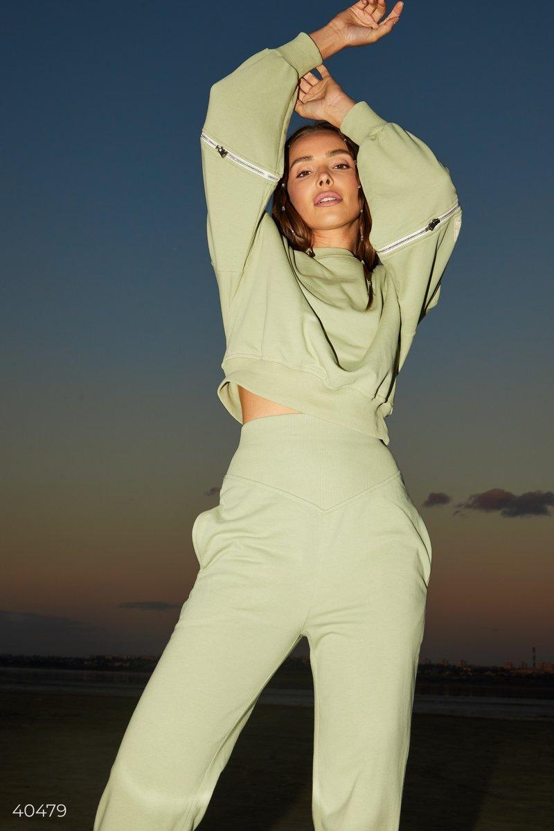 Базовый фисташковый свитшот, выполнен из смесового хлопка. Дизайнеры Gepur стилизовали модель молниями на рукавах, которые позволяют добавить модели изюминку, расстегнув их частично, или же полностью. Такой свитшот отлично будет смотреться с джинсами, или