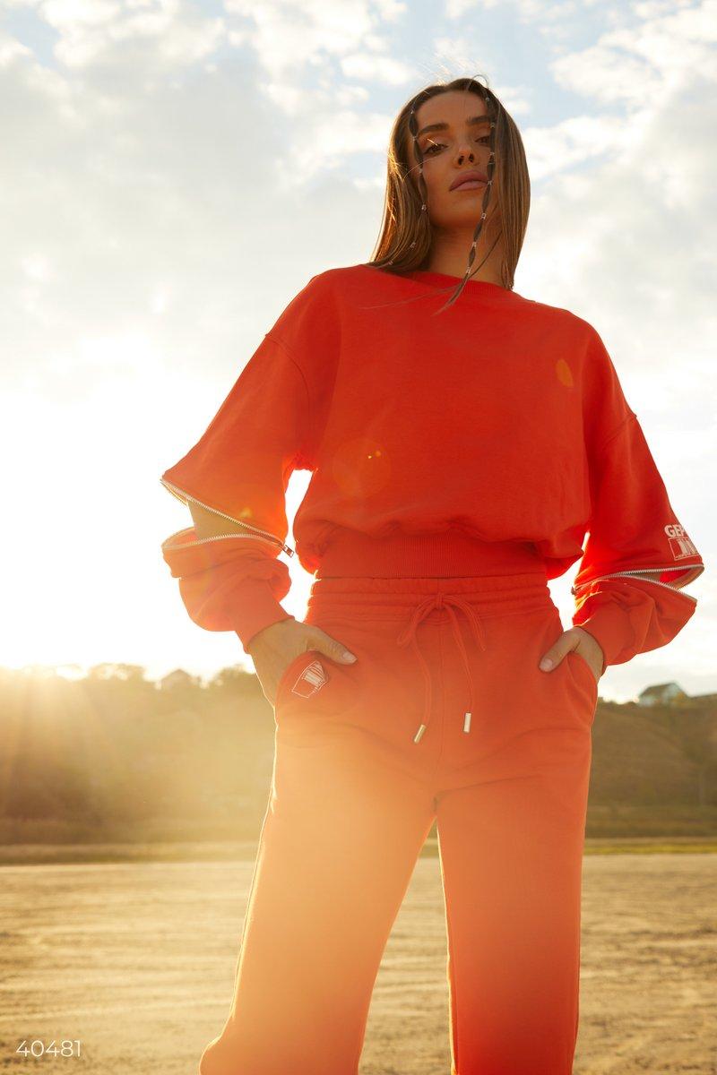 Яркий оранжевый свитшот, выполнен из смесового хлопка. Модель стилизована дизайнерами Gepur молниями на рукавах, которые позволяют добавить модели изюминку, расстегнув их частично, или же полностью. Такой свитшот отлично будет смотреться с джинсами, или т