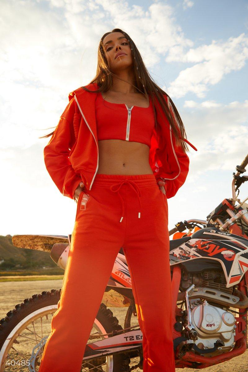 Оранжевое худи на молнии с капюшоном, стилизованным крупными шнурками. Модель представлена в ярком оранжевом цвете, укороченного кроя. Носите такую вещь поверх топов или футболок, с джинсами или джоггерами для создания комфортного образа на каждый день. П