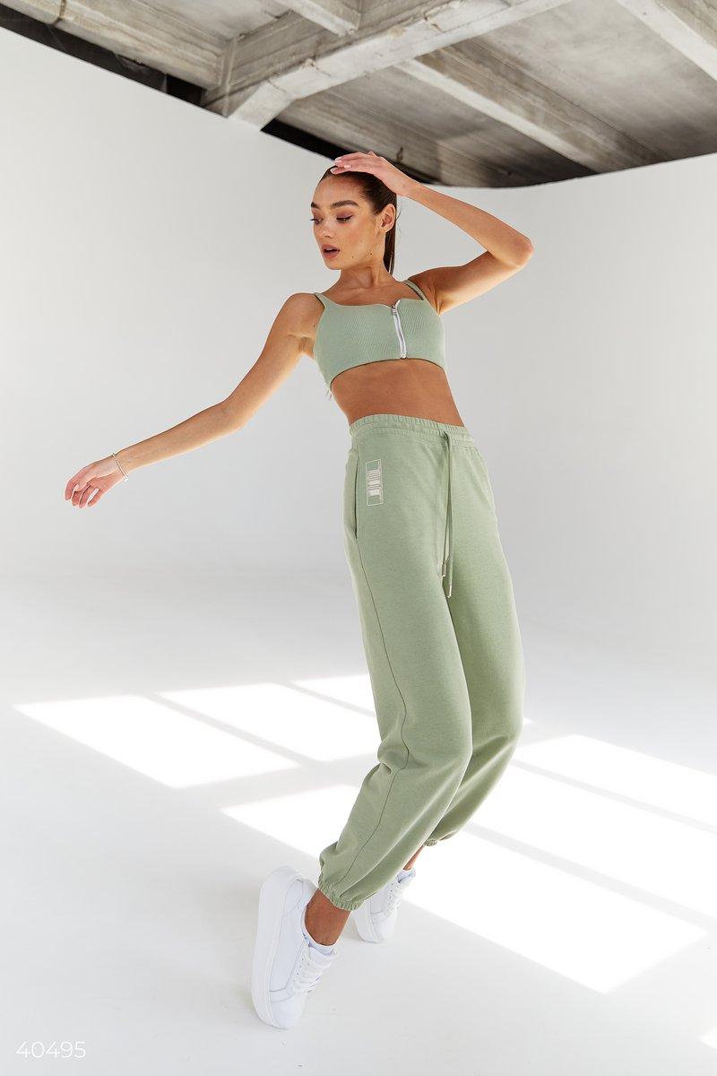 Трикотажные джоггеры фисташкового цвета от дизайнеров Gepur, выполнены из смесового хлопка. Модель представлена с эластичной вставкой в талии и по низу изделия, шнуровкой в поясе и карманами. Для создания спортивного образа вы можете сочетать джоггеры с т