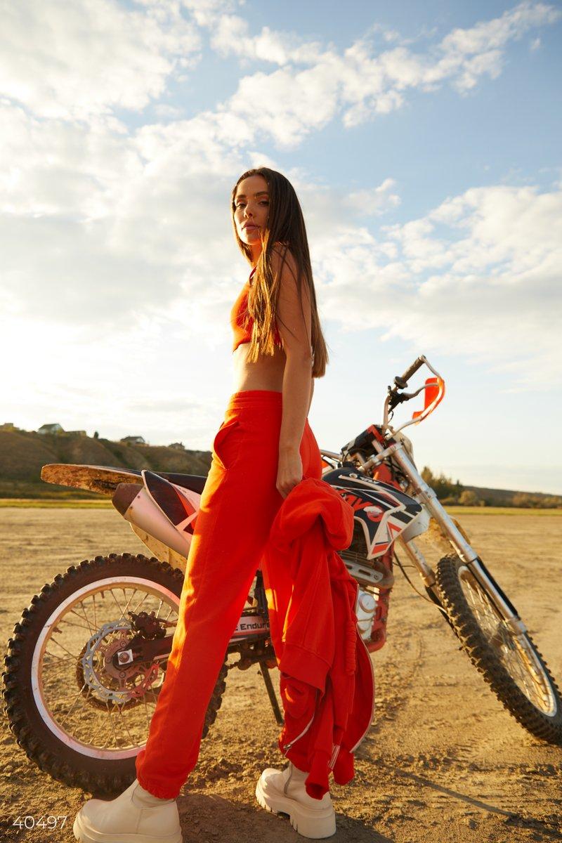 Трикотажные джоггеры оранжевого цвета от дизайнеров Gepur, выполнены из смесового хлопка. Модель представлена с эластичной вставкой в талии и по низу изделия, шнуровкой в поясе и карманами. Для создания спортивного образа вы можете сочетать джоггеры с тол