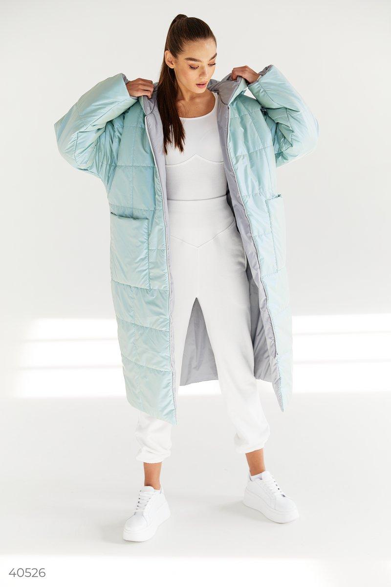 Теплый пуховик фисташкового цвета с перламутровым блеском длины ниже колена. Модель представлена с капюшоном, на молнии, с широким поясом в комплекте. В своих коллекциях тренд на oversize поддержали такие модные дома, как Isabel Marant, Prada и Michael Ko