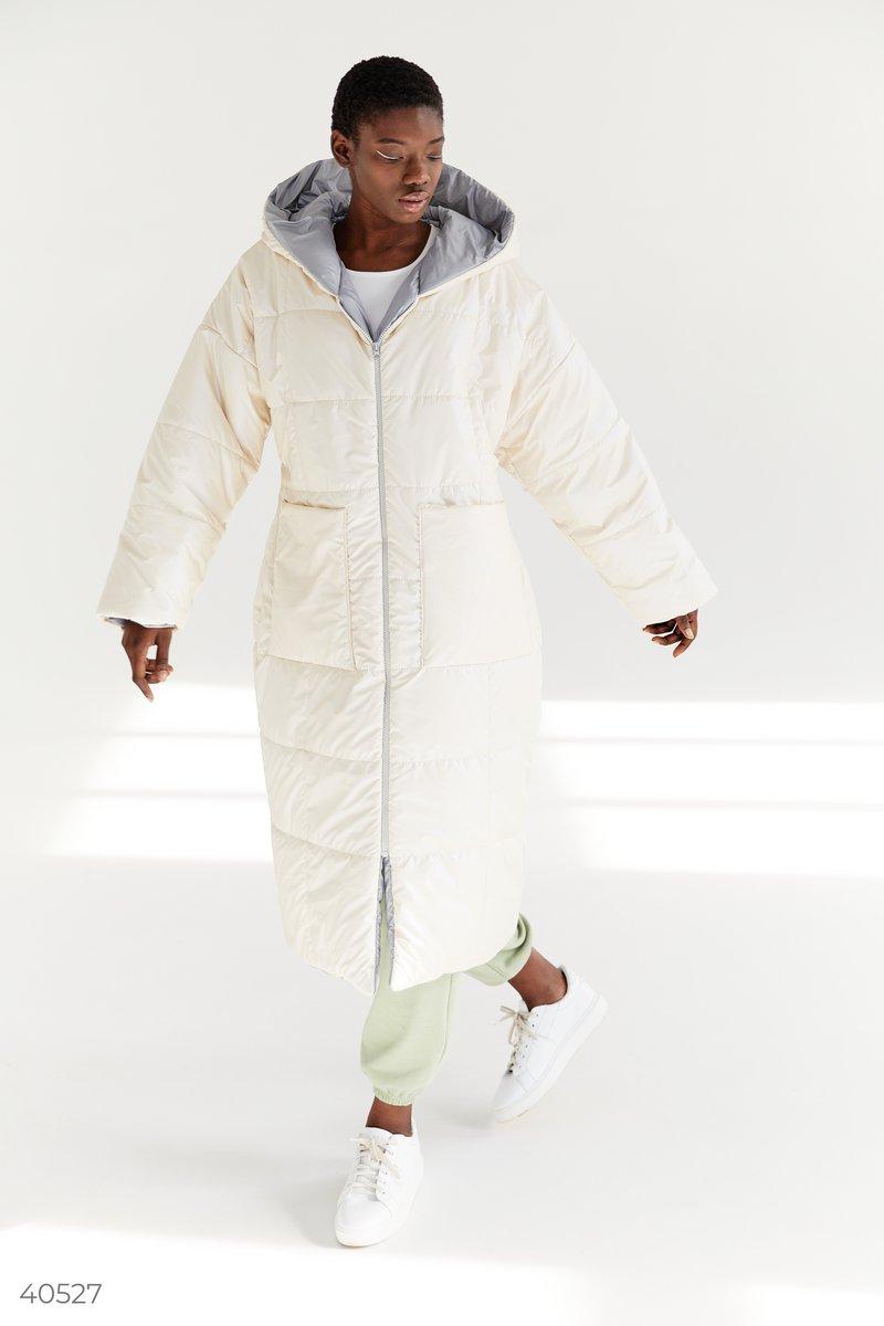 Теплый пуховик кремового цвета с перламутровым блеском длины ниже колена. Модель представлена с капюшоном, на молнии, с широким поясом в комплекте. В своих коллекциях тренд на oversize поддержали такие модные дома, как Isabel Marant, Prada и Michael Kors.