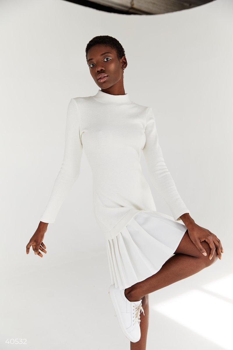 Платье мини выполнено из мягкого трикотажа в молочном цвете. Модель стилизована трендовой плиссировкой по низу изделия, что также создает актуальный эффект многоярусности. В своих коллекциях изделия с плиссе также представили такие модные дома, как Lacost